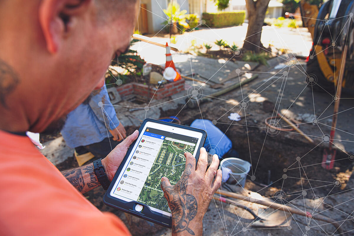 Santa Barbara field professional using Cartegraph One on an iPad while a crew repairs a burst pipe